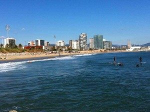 surfers with backdrop of barcelona apartments for sale